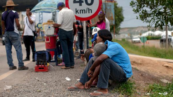 Venezuelan refugees wait outside the Brazilian Immigration Point in the border city of Pacaraima, Roraima, Brazil, on Aug. 20. Brazil's president said armed forces would be sent to the area.