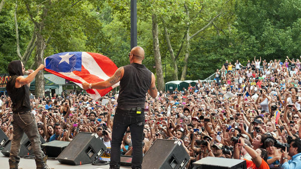 Wisin y Yandel wave the flag of Puerto Rico during a performance in Central Park on  August 13, 2011.