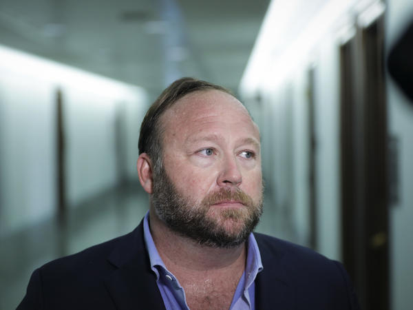 Alex Jones of InfoWars talks to reporters outside a Senate Intelligence Committee hearing on Wednesday. Twitter has permanently suspended the conspiracy theorist, citing violations of its policy on abusive behavior.