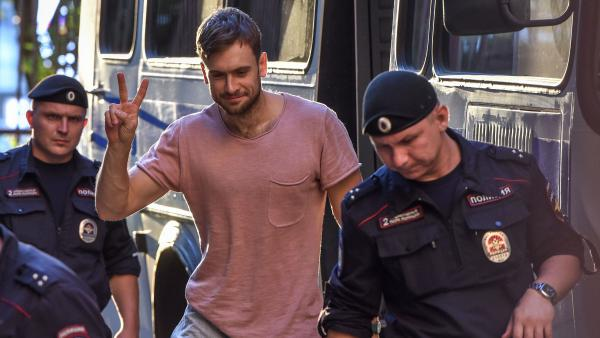 Pyotr Verzilov (center) walks to a court hearing related to Pussy Riot's rushing of the World Cup final pitch on July 15. The group suspects Verzilov was poisoned on Tuesday.