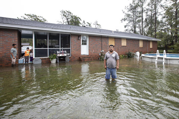Juan Diaz stands in his flooded back yard in Castle Hayne. The Diaz family hopes the rain will end soon; the water is only a few inches away from entering their first floor.