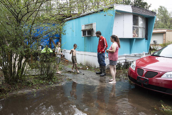 The Bland family gathers outside their home in Castle Hayne. Florence is enormous, slow and very, very wet. Storms get those qualities from warm ocean water and weak wind currents that allow them to suck up moisture and come to a gradual halt over land, dumping water everywhere.