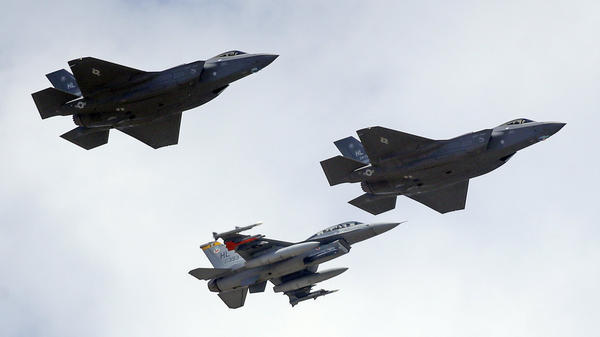 An F-16 escorts two F-35 fighter jets arriving at Hill Air Force Base in Utah. Each stealth F-35 costs about $90 million.