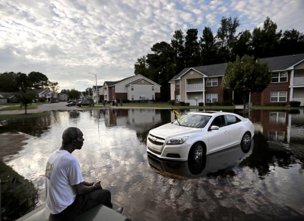 Augustin Dieudomme looks toward the flooded entrance of his apartment complex near the Cape Fear River in Fayetteville, N.C., on Tuesday, as the river continues to rise in the aftermath of Hurricane Florence.