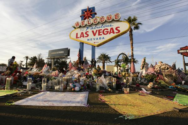People visit a makeshift memorial for victims of the mass shooting in Las Vegas in October 2017. Fifty-eight crosses were planted in front of the sign to commemorate each of the people killed in the attack.
