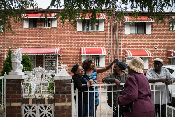 Ruth Palacio (from left), Shantel Palacio, Peter Palacio and Cyril Castillo greet a neighbor outside the Palacios' home in the Brownsville section of Brooklyn, N.Y.