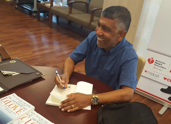 Dr. B.S. Kesavan greets another well-wisher during his book signing at Cottage Hospital.