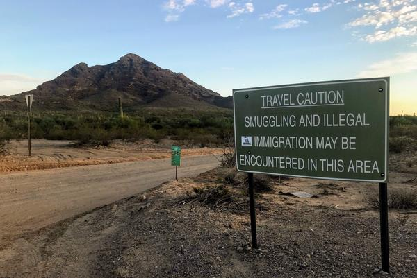 """A sign outside Ajo, Ariz., warns hikers to keep an eye out for people who have unlawfully crossed the nearby border with Mexico. No More Deaths and other humanitarian groups use a private residence they call """"the barn"""" on the outskirts of the small town as a base of operations."""