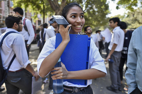 A girl talks on her mobile phone after coming out of class in New Delhi.