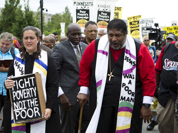 The Rev. William Barber marches outside the U.S. Capitol during a Poor People's Campaign rally in June. On the left is co-leader of the Poor People's Campaign, the Rev. Liz Theoharis.