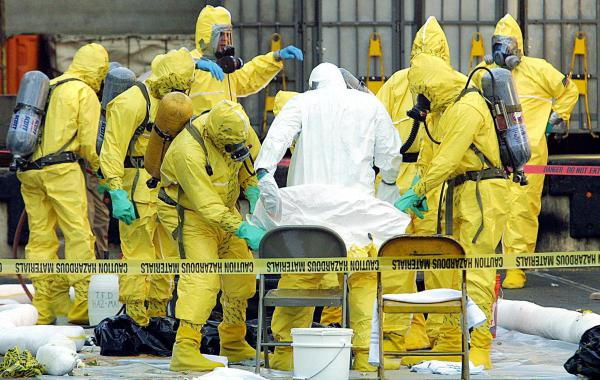 Members of a haz-mat team help remove a hazardous materials suit from an investigator (in white) who emerged from the U.S. Post Office in West Trenton, N.J., on Oct. 25, 2001. Samples from the facility were part of an investigation into letters containing anthrax.