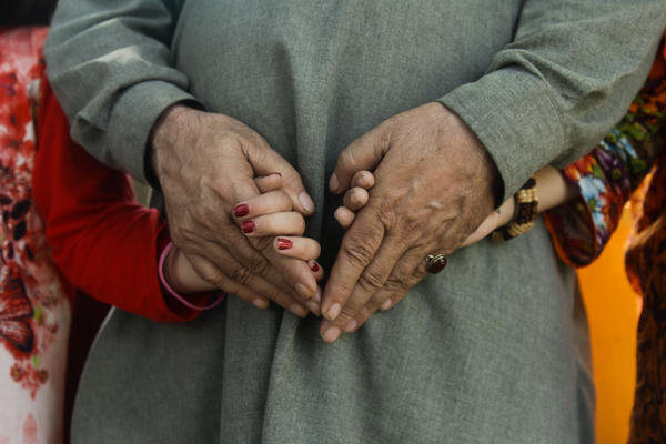"Mir, a Pakistani man who used to live in Xinjiang, China, clutches the hands of his two daughters. Since Chinese authorities detained his wife, he's been raising their two girls alone. ""My mind just won't work,"" he says. ""I sound incoherent, I can't think, I even forget what to say in my prayers."""