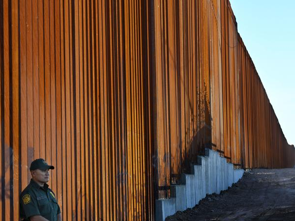 A border protection officer stands next to a recently upgraded section of fencing at the U.S.-Mexico border in Calexico, Calif., on Friday. The Pentagon says it will send 5,000 U.S. troops to the border.