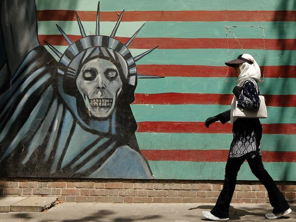 An Iranian woman walks past the former U.S. Embassy in Tehran, which bears a mural depicting the Statue of Liberty with a dead face. With just days to go until the U.S. plans to snap more sanctions back into place, questions linger about what the move spells for the world.