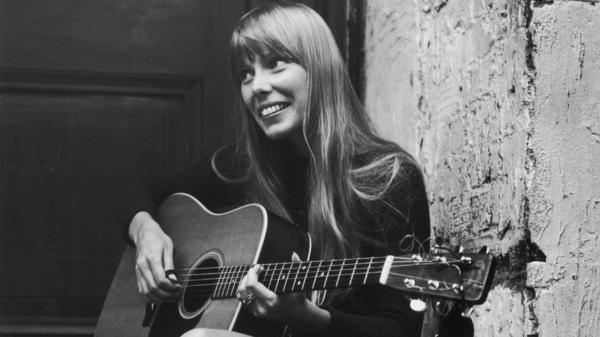 Joni Mitchell strums her guitar outside The Revolution club in London in 1968.