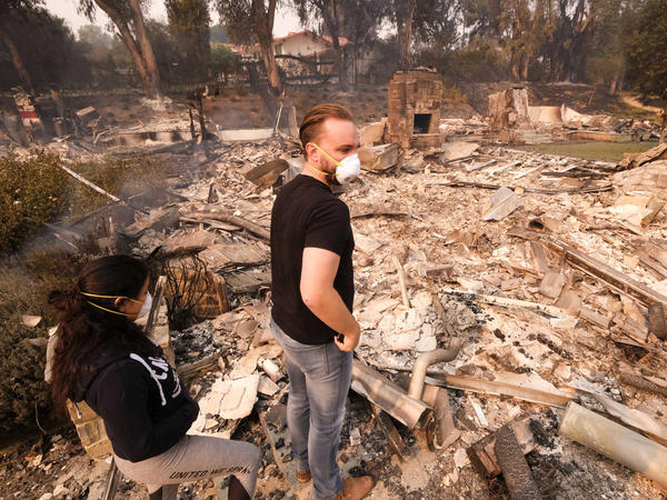 A California man and his girlfriend return to his burned-out home in Malibu on Saturday.