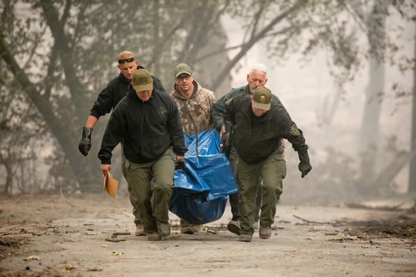 Yuba County Sheriff officers carry a body away from a burned residence in Paradise, California.