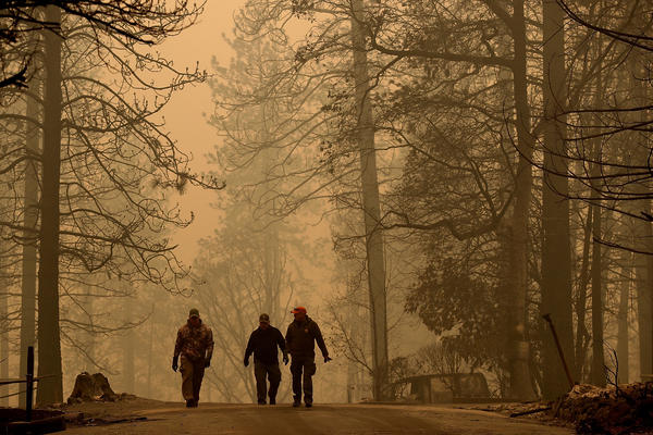 Sheriff deputies walk through a neighborhood destroyed by the Camp Fire near Paradise, California.
