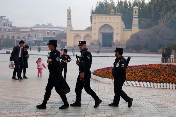 "Uighur security personnel patrol near the Id Kah Mosque in Kashgar, a city in northwestern China's Xinjiang region, in 2017. Xinjiang authorities have detained members of the Uighur ethnic minority, who are largely Muslim, and held them in camps the authorities call ""education and training centers."""