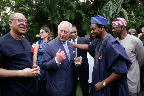 Prince Charles speaks with a guest at an event in Lagos, Nigeria, where he delivered a speech using phrases in pidgin English.
