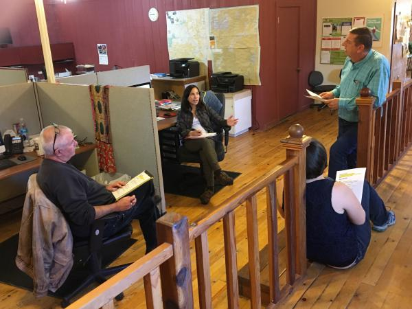 <em>Malheur Enterprise</em> reporters Pat Caldwell (from left) and Kristine de Leon; Les Zaitz, editor and publisher; and, sitting on the floor, reporter Jayme Fraser meet to talk about assignments.