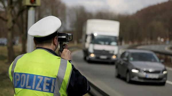 A police officer in Wuppertal, Germany, measures the speed of passing cars with a laser pistol in March.