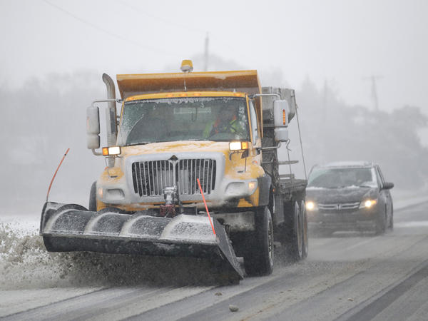 A plow clears snow from Road 438 in Douglas County near Lawrence, Kan., on Sunday. The area is under a blizzard warning.