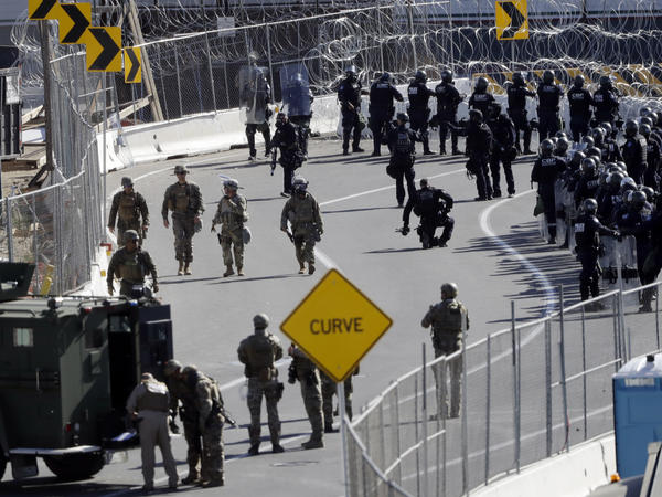Military personnel and Customs and Border Protection officers gather at the San Ysidro Port of Entry in San Diego. The number of immigrants in the U.S. without legal status has declined to its lowest level in more than a decade, according to a new report released Tuesday.