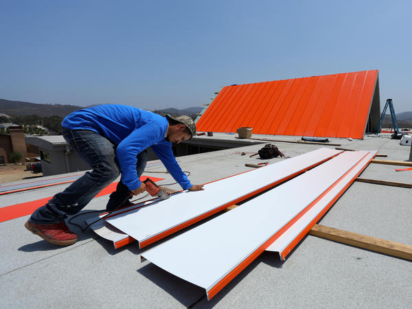 A worker installs a roof on a home being built in San Diego in 2017. The housing market has been softening, with sales of new single-family homes falling in October to the lowest level in more than 2 1/2 years.