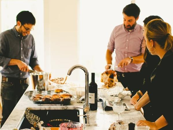 Michael Durand (left), husband of Kitchn Editor-In-Chief Faith Durand, and friend Chris Gardner (right) carve turkey while guests hang out in the Durands' kitchen, dirty dishes and all, at a recent party.