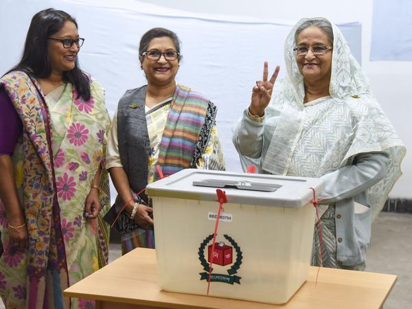 Bangladeshi Prime Minister Sheikh Hasina flashes the victory symbol after casting her vote, as her daughter Saima Wazed Hossain (far left) and her sister Sheikh Rehana look on.