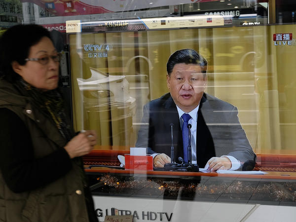 "A woman walks past a television in New Taipei City showing China's leader Xi Jinping making a speech commemorating the 40th anniversary of a message sent to Taiwan in 1979. In his speech, Xi Jinping said Taiwan's unification with the mainland is ""inevitable"" and warned against any efforts to promote the island's independence."