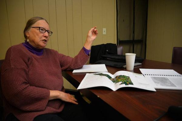 <p>Environmental activist Jean Mendoza studies maps of monitoring wells in the Lower Yakima Valley. Mendoza has worked on a groundwater advisory committee for the last six years to develop a plan to reduce nitrates in drinking water.</p>