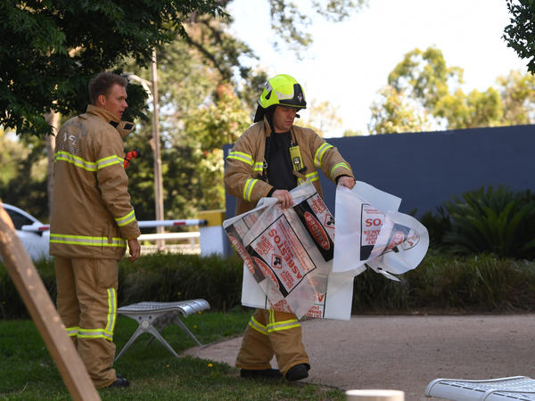 "A firefighter carries a hazardous material bag into the Korean consulate in Melbourne. Several foreign consulates in southeastern Australia were evacuated Wednesday as emergency workers responded to multiple ""hazardous material"" events in the city."