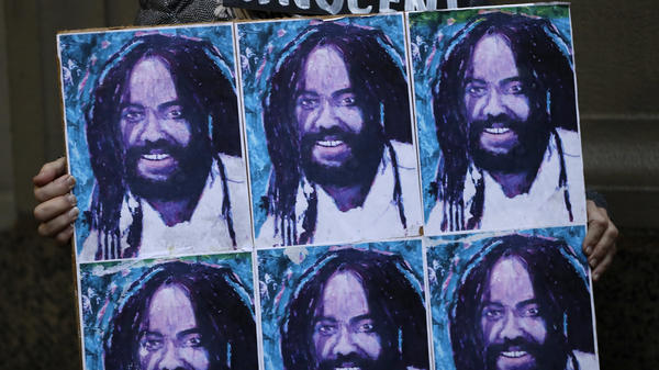A protestor holds up a poster depicting Mumia Abu-Jamal during a demonstration outside the offices of District Attorney Larry Krasner, Friday, Dec. 28, 2018, in Philadelphia.
