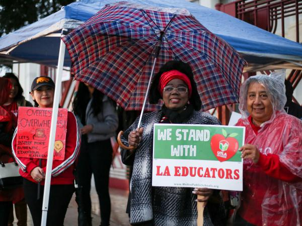 """Educators from Hollenbeck Middle School in Boyle Heights, Los Angeles chant, """"Teachers united will never be defeated!"""" in front of their school."""