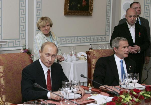 """In a 2006 photo, Russian President Vladimir Putin (left) hosts U.S. President George W. Bush in St. Petersburg, Russia. At second right is Russian businessman Yevgeny Prigozhin, known as """"Putin's chef."""" The U.S. has charged Prigozhin with running an Internet operation that interfered with the 2016 U.S. presidential election. He's also been sanctioned for supporting Russia's occupation in Ukraine."""