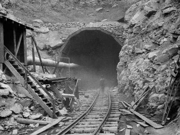 In the photo above, dust circles a worker during the construction of the Hawks Nest Tunnel in 1930. Workers on the project were exposed to toxic levels of silica dust; hundreds ultimately died.