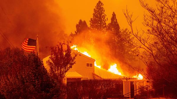 "A home burns during the Camp Fire in Paradise, Calif., in November 2018. It was one of several fires often discussed in terms of the changing climate. A new survey shows a jump in the number of Americans who are ""very worried"" about global warming."