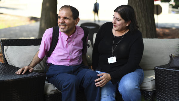 Angela Disisto of Medford, Mass., sits with her brother, Luigi, who has autism, at the Judge Rotenberg Educational Center in Canton, Mass. The backpack Luigi is wearing carries equipment that would give him a two-second electric skin shock if staff deem his behavior dangerous.