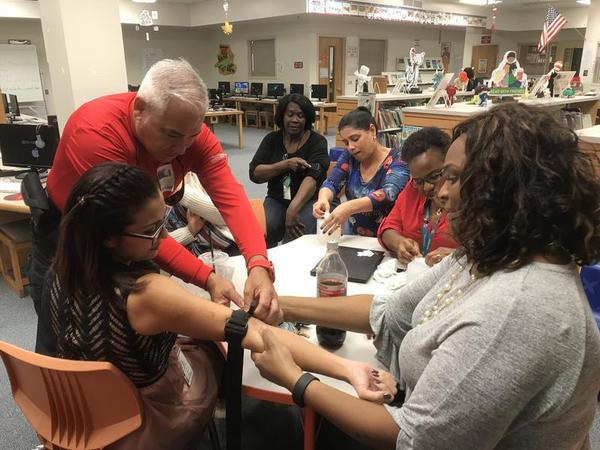 Miramar Fire Rescue officials help teachers practice how to use tourniquets during a training in bleeding control at Coral Cove Elementary School on Oct. 31.