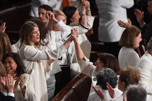 Congresswomen, dressed in white in tribute to the women's suffrage movement, applaud.