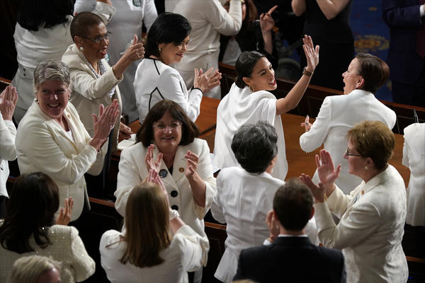 Democratic female lawmakers, dressed in white as a tribute to suffragettes, applaud at President Trump's State of the Union address.