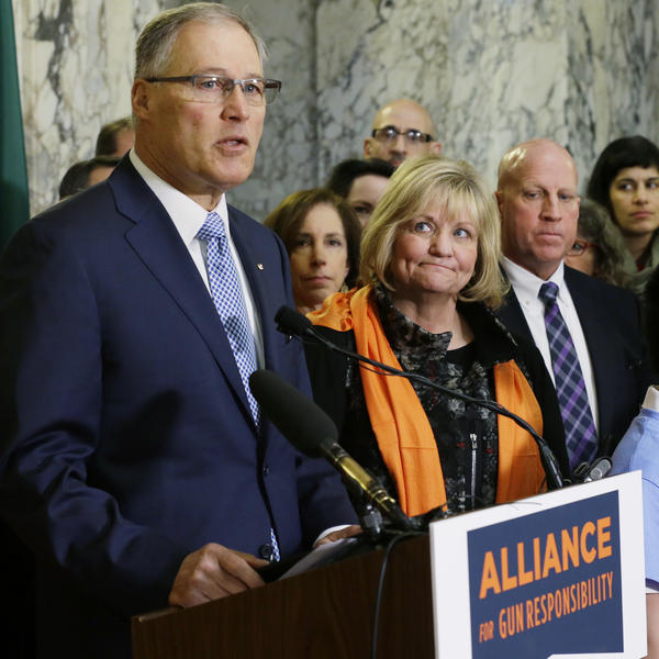 Washington Gov. Jay Inslee speaks in support of firearm restrictions in 2017, as his wife, Trudi, looks on. The initiative passed, but some Washington state sheriffs are refusing to enforce all the measures.