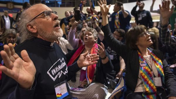 Protesters sing and pray outside the United Methodist Church's special session of the general conference in St. Louis on Tuesday. Delegates voted to maintain current rules against LGBTQ clergy and same-sex marriage.