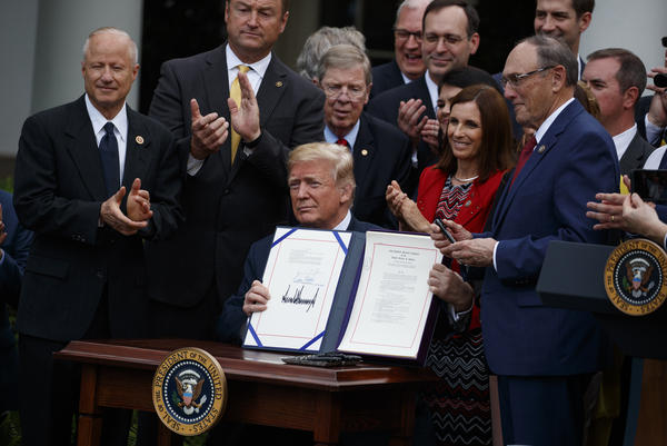President Trump shows off the VA Mission Act during a signing ceremony in the Rose Garden of the White House last June.