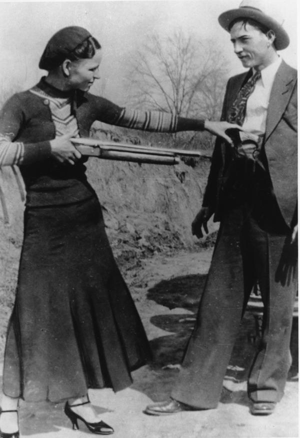 Bonnie Parker playfully aims a gun at Clyde Barrow.