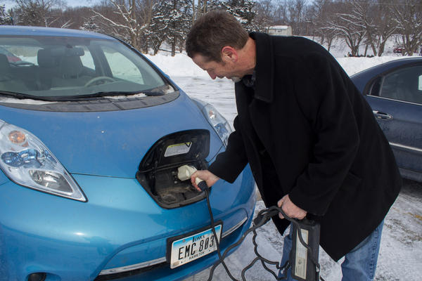 Nissan Leaf owner Rand Faaborg demonstrates how he attaches the electric cord to his car. The other end can be plugged into any standard 110-volt outlet.