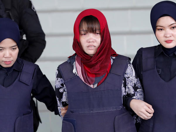 Vietnamese Doan Thi Huong, center, is escorted by police as she leaves Shah Alam High Court in Malaysia on Thursday. Malaysia's attorney general ordered the murder case to proceed against the Vietnamese woman accused in the killing of the North Korean leader's estranged half brother.