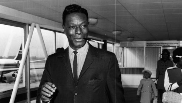 Nat 'King' Cole having a smoke while disembarking from a plane in 1963.